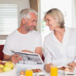Mature couple reading newspaper while having breakfast at home